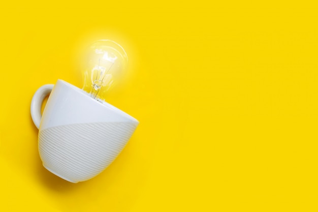 Bombilla en la taza blanca sobre fondo amarillo. ideas y concepto de pensamiento creativo. copia espacio