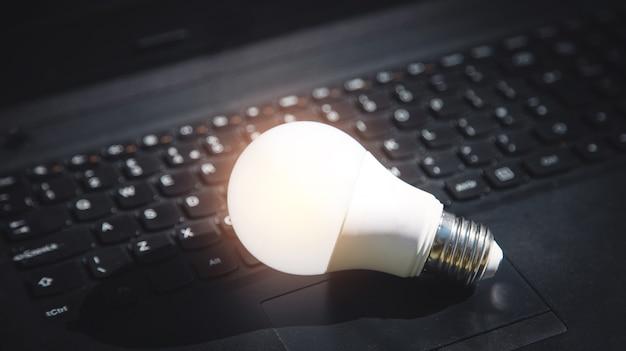 Bombilla en el teclado de la computadora portátil. idea, innovación, creatividad