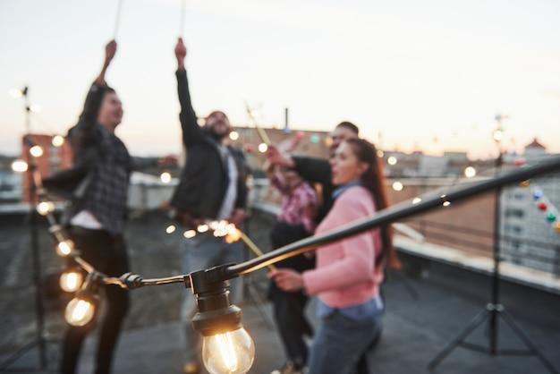 Las bombillas están encendidas. foto enfocada jugando con bengalas en la azotea. grupo de jóvenes amigas hermosas