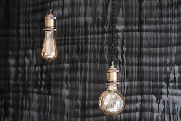 Bombillas de luz edison antiguas de estilo decorativo en el fondo de la pared gris oscuro. detalles interiores de loft, decoración en restaurante en boda.
