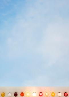 Bombillas de luz iluminadas de colores contra el cielo azul