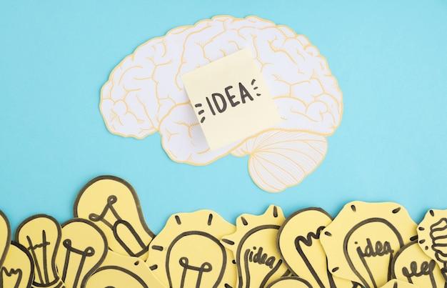Las bombillas de papel recortadas y el texto de la idea en el cerebro sobre el fondo azul