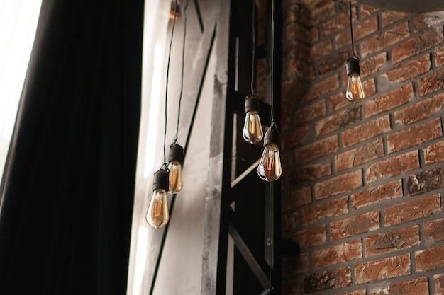 Bombillas de tungsteno de luz de estilo edison antiguo decorativo contra el fondo de la pared de ladrillo