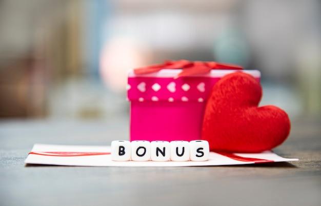 Bonificación de la tarjeta en un sobre de papel. caja de regalo. sorpresa y corazón rojo para el ánimo.