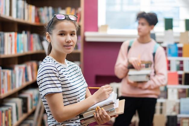 Bonita adolescente con pila de libros y lápiz mirándote mientras está de pie en la biblioteca de la universidad con un compañero de clase