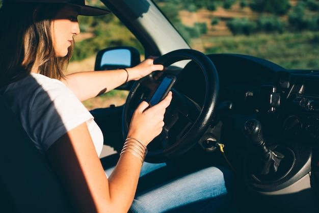 Bonita y atractiva chica rubia con gorra conduciendo con teléfono en furgoneta naranja