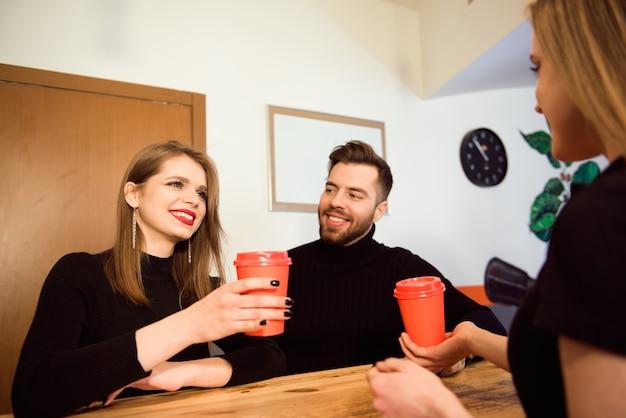 Bonita barista sonriendo y sosteniendo vasos desechables en una cafetería.