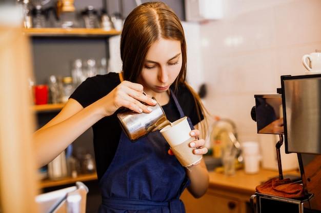 Bonita barista vertiendo leche en una taza de café en la cafetería.
