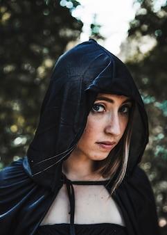 Bonita bruja en capucha negra en matorral iluminado por el sol