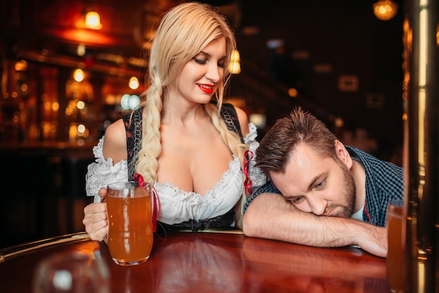 Bonita camarera con jarra de cerveza mira borracho en el mostrador de pub