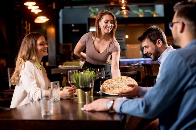 Bonita camarera sirviendo a un grupo de amigos con comida en el restaurante