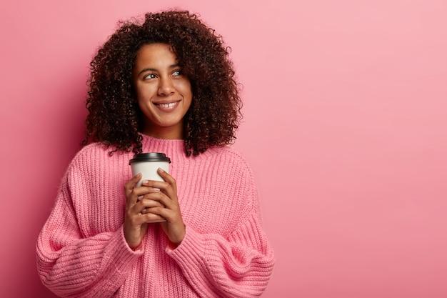 Bonita chica afro sostiene una taza de café de papel, disfruta del tiempo libre, mira con una sonrisa a un lado, usa un jersey de gran tamaño