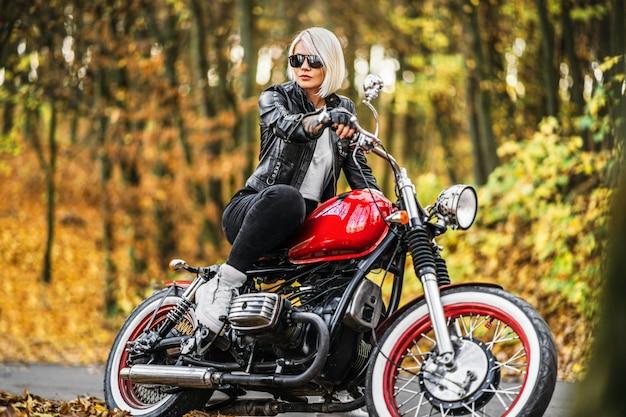 Bonita chica biker rubia en gafas de sol con moto roja en la carretera en el bosque