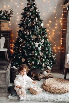 Bonita chica caucásica con el pelo rizado se sienta cerca de un gran árbol de navidad hermoso