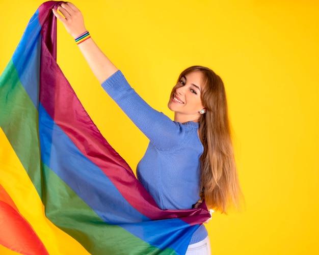 Bonita chica lesbiana rubia con bandera del orgullo gay en la pared de color amarillo pastel