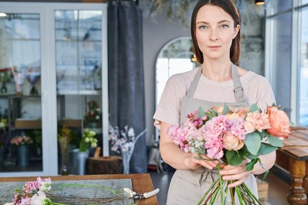 Bonita chica morena en ropa de trabajo de pie delante de la cámara mientras prepara flores frescas para racimos