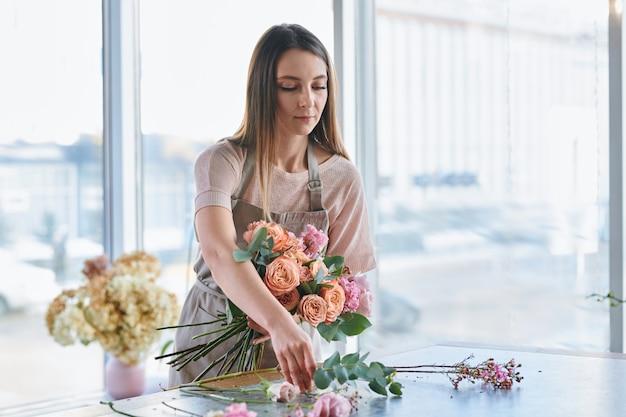 Bonita chica morena sacando una de las rosas frescas de la mesa mientras hacía racimos florales en su estudio
