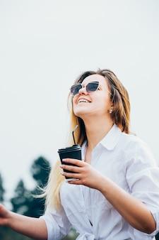 Una bonita chica de pelo largo con gafas de sol con una bebida, sonriendo
