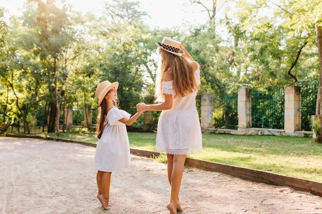 Bonita chica de pelo oscuro con sombrero de paja de pie de puntillas y mirando a los ojos de la madre disfrutando del buen tiempo en el parque. mujer joven delgada escalofriante en el jardín de la mano con el niño.