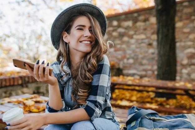 Bonita chica riendo con smartphone tiene un buen rato en fin de semana de otoño