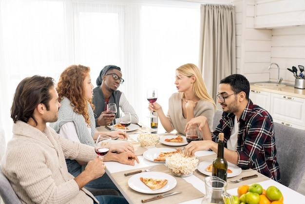 Bonita chica rubia con una copa de vino sentada entre sus amigos por la mesa servida y pronunciando un brindis de celebración por el almuerzo