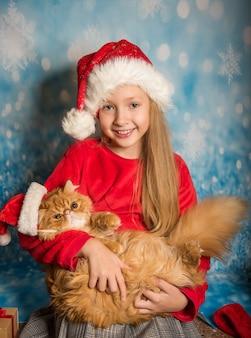 Bonita chica rubia con niño en rojo sombrero de santa con gato aislado sobre fondo azul nieve. concepto de navidad