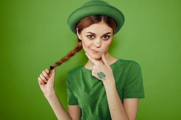 Bonita chica con un trébol en la mano en un sombrero divertido del día de san patricio de vacaciones verdes en la cabeza