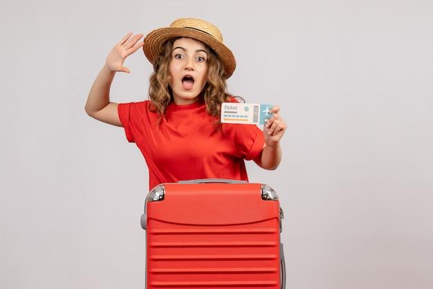 Bonita chica de vacaciones con su valija sosteniendo el boleto