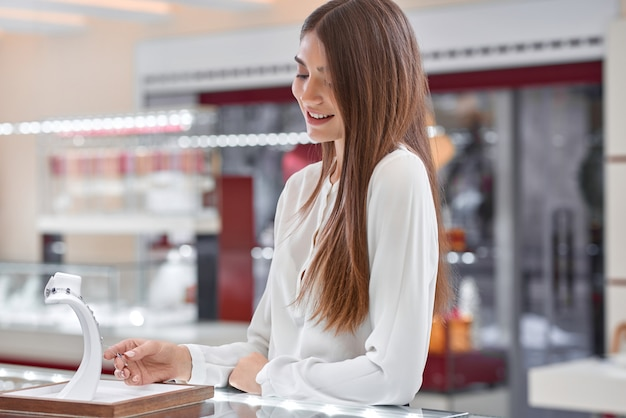 Bonita clienta está sonriendo mientras mira el collar en una joyería