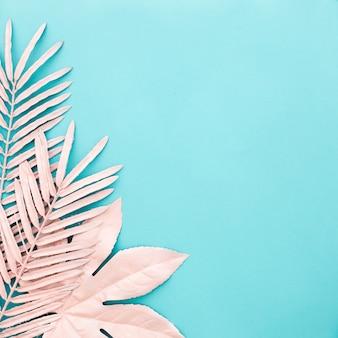 Bonita composición cuadrada de hojas de color rosa sobre fondo azul.