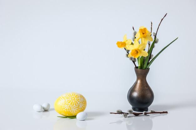 Bonita composición con huevo pintado y ramo de flores primaverales.