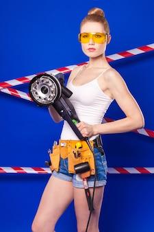 Bonita y delgada chica de construcción con camisa blanca, cinturón de construcción, gafas de construcción, pantalones cortos de jean y risitas con sierra eléctrica