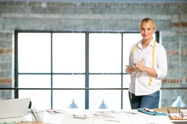Bonita diseñadora de moda haciendo notas o bocetos en el bloc de notas mientras está de pie junto al lugar de trabajo en el estudio