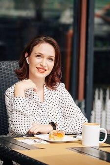Bonita empresaria sentado en la mesa de café