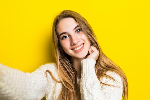 Bonita y encantadora niña de moda sonriente está haciendo selfie en su teléfono con un suéter blanco ancho en amarillo