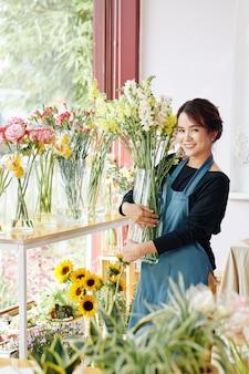 Bonita florista con jarrón de flores