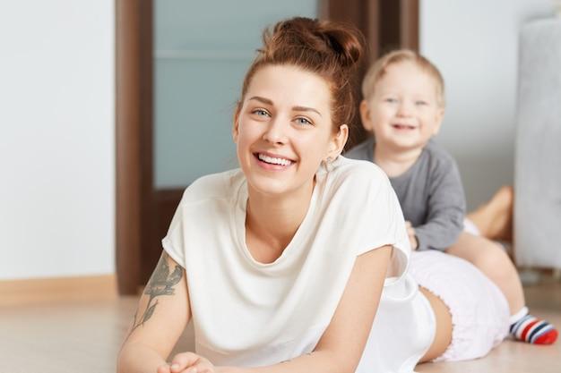 Bonita foto familiar de la joven madre y su pequeño hijo jugando en el suelo en casa. atractiva mujer caucásica en top blanco, acostada sobre su vientre. niño sonriente a horcajadas felizmente sobre su mamá brillante.