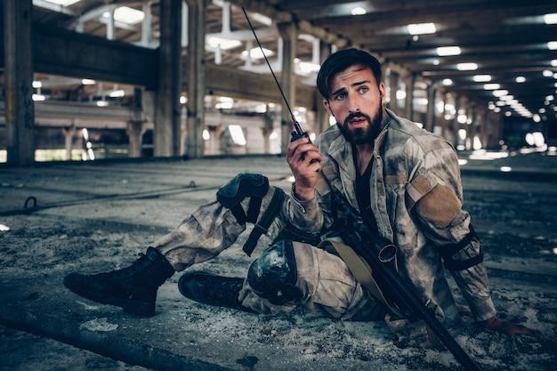 Bonita foto de morena atractiva y guapa sentada en el suelo. él está sosteniendo la radio portátil en la mano izquierda. rifle está acostado sobre su pierna izquierda. guy está mirando a la derecha.