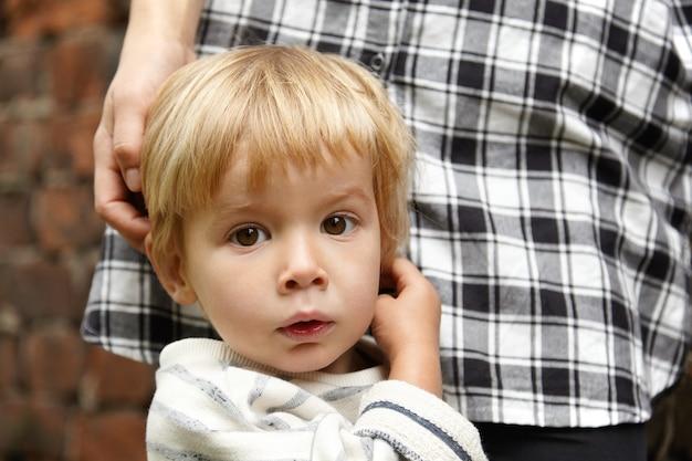 Bonita foto de niño rubio inocente con ojos marrones. hermosa expresión facial infantil con la boca ligeramente abierta. bebé de pie junto a la joven madre en camisa a cuadros. mamá acariciando la cabeza del niño cerca de la pared de ladrillo.