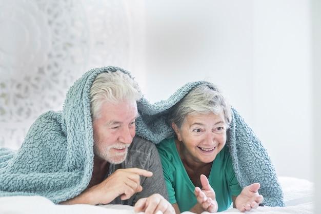 Bonita y hermosa pareja alegre de adultos mayores jubilados jugar juntos bajo la manta en casa