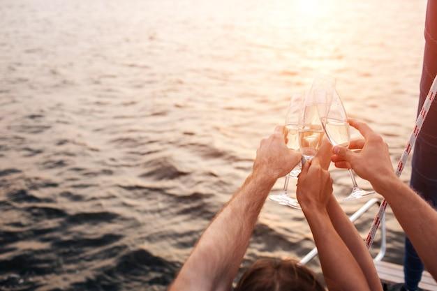 Bonita imagen de cuatro manos sosteniendo vasos de champán frente al agua