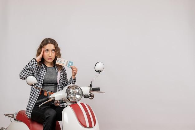 Bonita joven en ciclomotor sosteniendo el boleto en gris