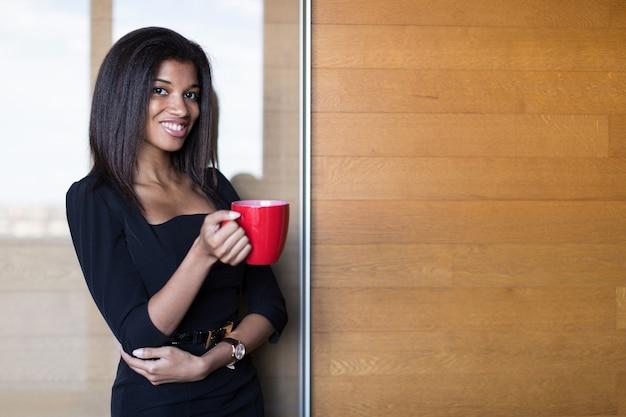Bonita y joven dama de negocios en suite negra fuerte sostenga la taza roja