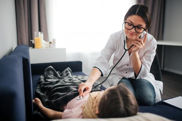 Bonita joven doctora escucha la respiración del niño a través del estetoscopio. ella sonríe y mira a la chica. el doctor se sienta además. niño recostado en el sofá.