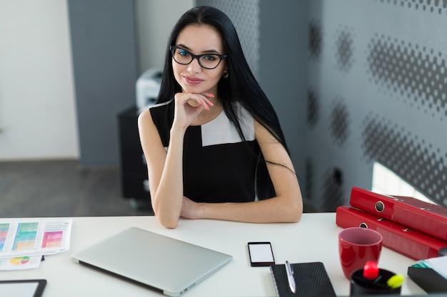 Bonita, joven empresaria en vestido negro y anteojos se sienta a la mesa y trabaja