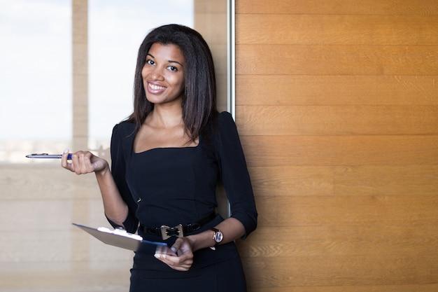 Bonita, joven mujer de negocios en tableta negra fuerte suite hold