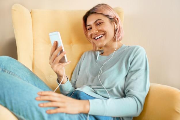 Bonita jovencita relajante en casa charlando con amigos en línea en el móvil a través de una llamada grupal por webcam, sonriendo. linda mujer joven sentada en un sillón con teléfono celular y auriculares, viendo videos divertidos