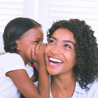 Bonita madre sentada en el sofá con su hija susurrando un secreto
