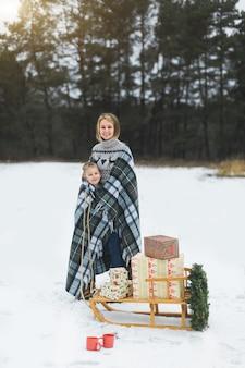 Bonita madre con su hijo de pie sobre el fondo del bosque, tirando de un trineo de madera