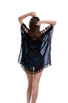 Bonita modelo morena tonificada posando desde atrás en traje de baño floral y pareo azul oscuro